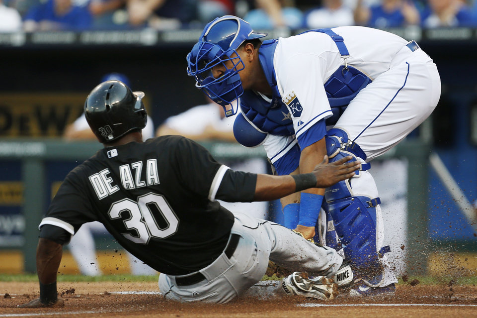 Photo - Chicago White Sox's Alejandro De Aza (30) is tagged out by Kansas City Royals catcher Salvador Perez, right, during the first inning of a baseball game at Kauffman Stadium in Kansas City, Mo., Friday, June 21, 2013. (AP Photo/Orlin Wagner)