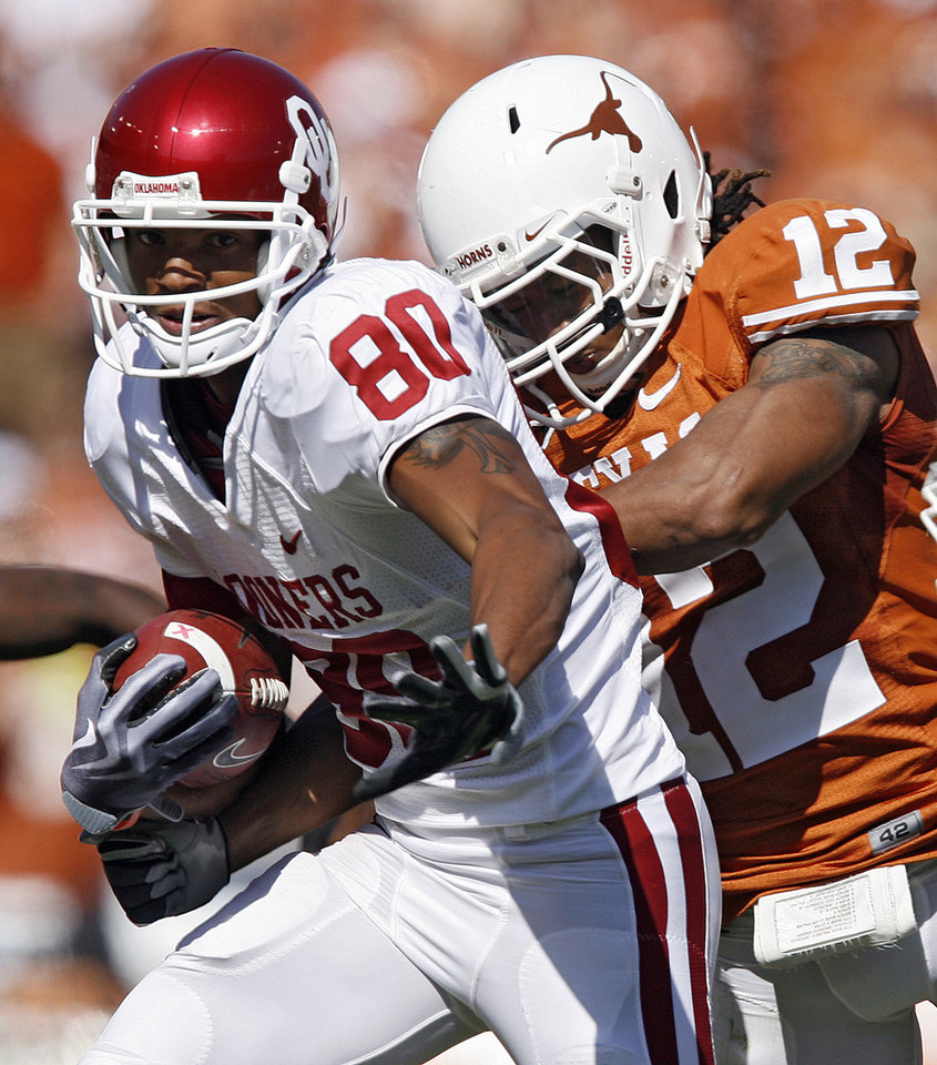 Photo - Adron Tennell (80) takes the ball up field after a reception against Texas' Earl Thomas (12) during the Red River Rivalry college football game between the University of Oklahoma Sooners (OU) and the University of Texas Longhorns (UT) at the Cotton Bowl in Dallas, Texas, Saturday, Oct. 17, 2009. Photo by Chris Landsberger, The Oklahoman