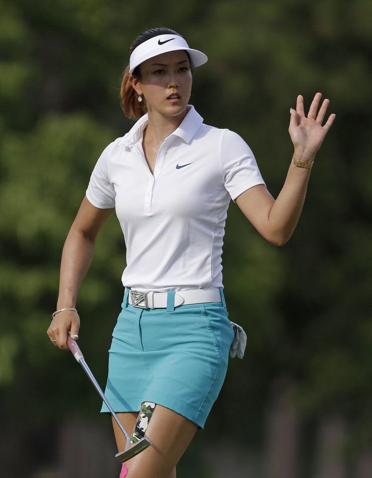 Photo - Michelle Wie waves after making a putt on the 14th hole during the first round of the LPGA U.S. Women's Open golf tournament in Pinehurst, N.C., Thursday, June 19, 2014. (AP Photo/Bob Leverone)