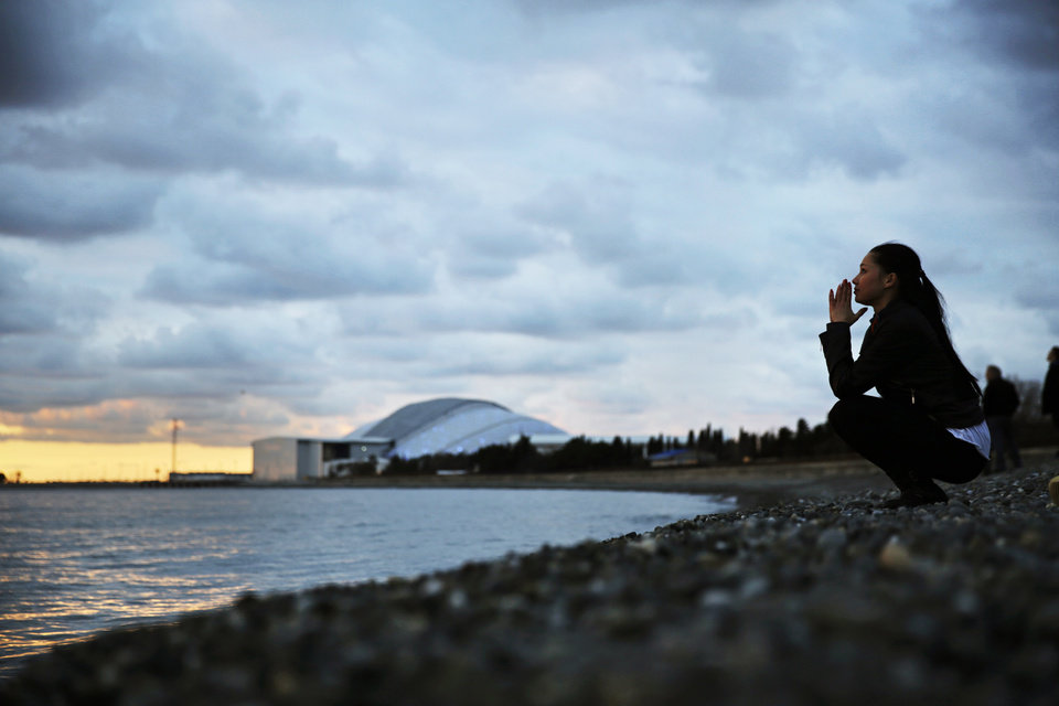 Photo - Elina Suyundikova, a dancer in the 2014 Winter Olympics opening ceremony, watches the sunset along the Black Sea while returning from a rehearsal on the eve of the performance and the games' official opening at Fisht Olympic Stadium, seen in the background, Thursday, Feb. 6, 2014, in Sochi, Russia. (AP Photo/David Goldman)