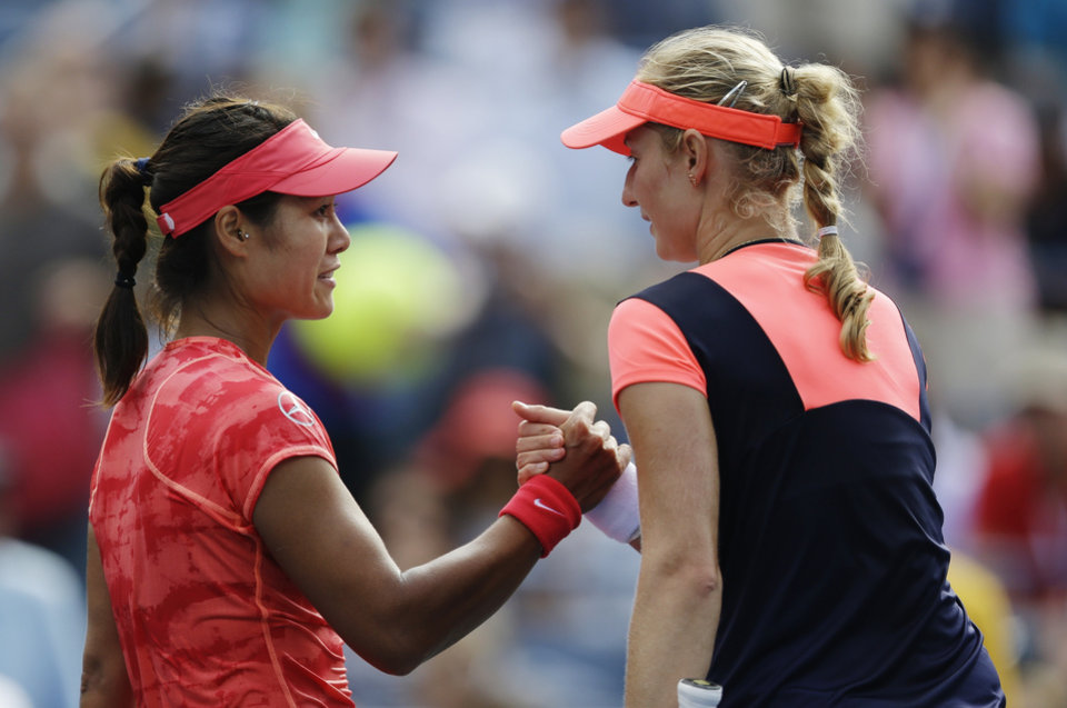 Photo - Li Na, of China, greets Ekaterina Makarova, of Russia, at the net after winning their quarterfinal match at the 2013 U.S. Open tennis tournament, Tuesday, Sept. 3, 2013, in New York. (AP Photo/Julio Cortez)
