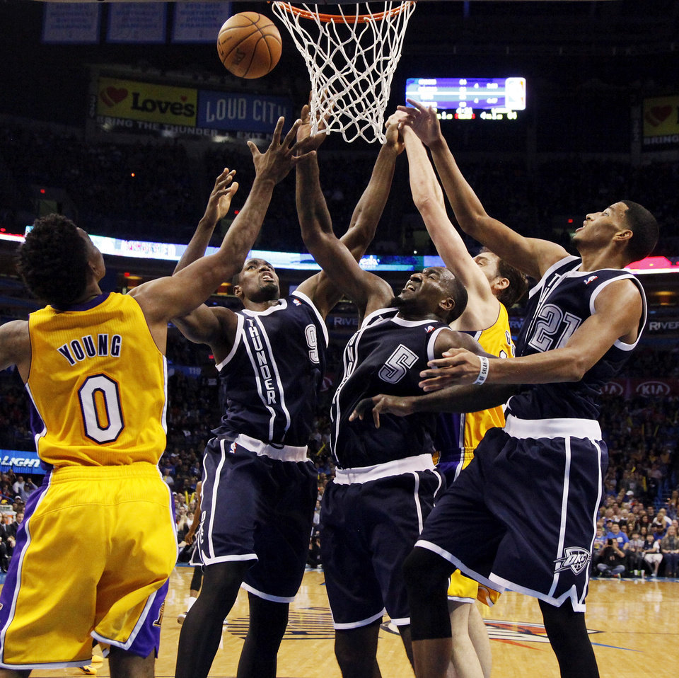 Photo - From left, LA's Nick Young (0), Oklahoma City's Serge Ibaka (9), Oklahoma City's Kendrick Perkins (5), LA's Pau Gasol (16) and Oklahoma City's Andre Roberson (21) try to grab a rebound during an NBA basketball game between the Los Angeles Lakers and the Oklahoma City Thunder at Chesapeake Energy Arena in Oklahoma City, Friday, Dec. 13, 2013. OKC won, 122-97. Photo by Nate Billings, The Oklahoman