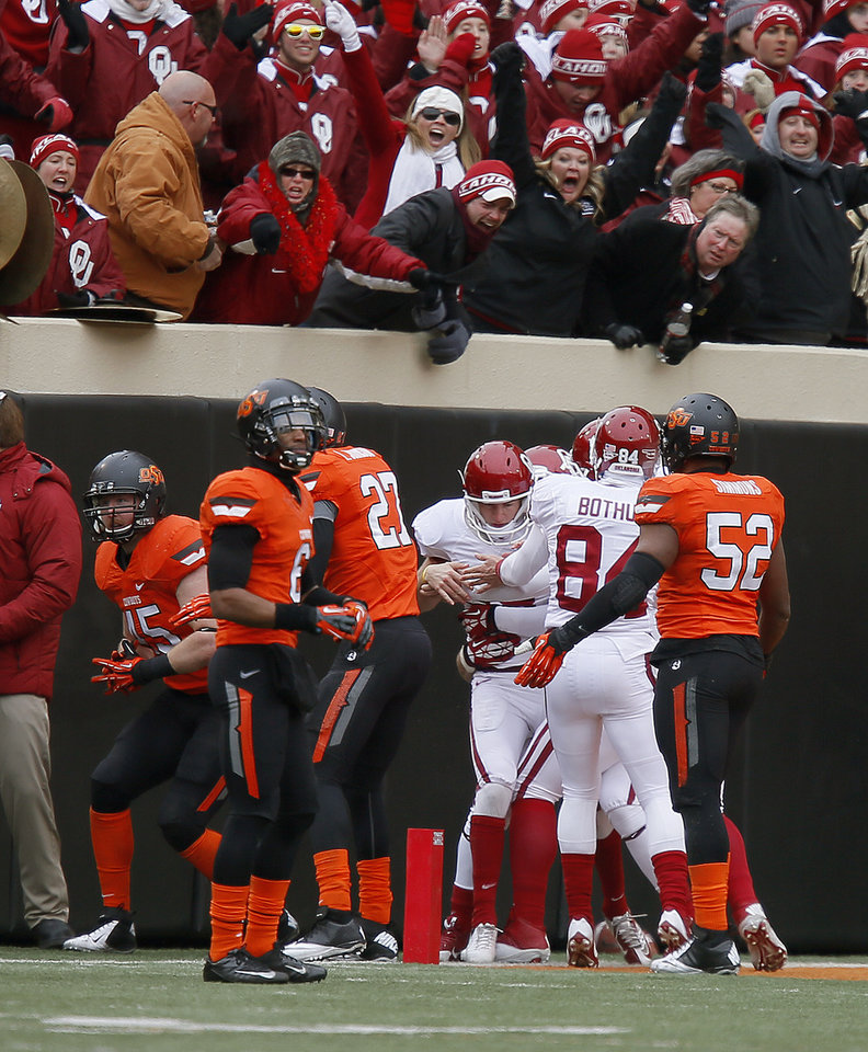Photo - Oklahoma players celebrate with Oklahoma's Michael Hunnicutt after he scored on a fake field goal during the Bedlam college football game between the Oklahoma State University Cowboys (OSU) and the University of Oklahoma Sooners (OU) at Boone Pickens Stadium in Stillwater, Okla., Saturday, Dec. 7, 2013. Oklahoma won 33-24. Photo by Bryan Terry, The Oklahoman