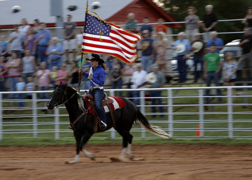 Photo - Edmond Round Up Club Queen Jessi Malone carries the American flag into the arena before the annual LibertyFest Rodeo in Edmond. PHOTO BY BRYAN TERRY, THE OKLAHOMAN.  Bryan Terry - THE OKLAHOMAN