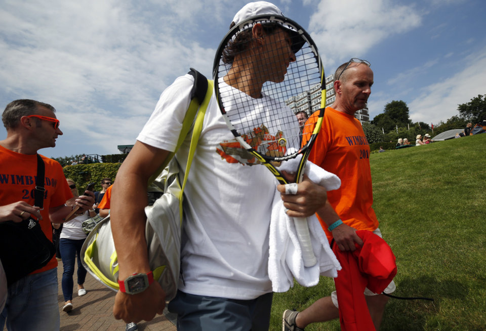 Photo - Rafael Nadal of Spain walks through the grounds with members of the public on the first day at the All England Lawn Tennis Championships in Wimbledon, London, Monday June 23, 2014. (AP Photo/Pavel Golovkin)