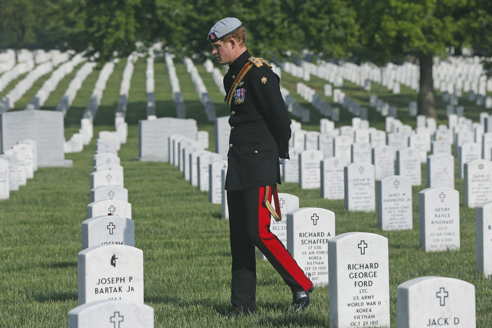 Photo - England's Prince Harry visits Section 60 at Arlington National Cemetery, Friday, May 10, 2013. The British soldier-prince is spending most of his week in the U.S. honoring the wounded and the dead of war. (AP Photo/Charles Dharapak, Pool)
