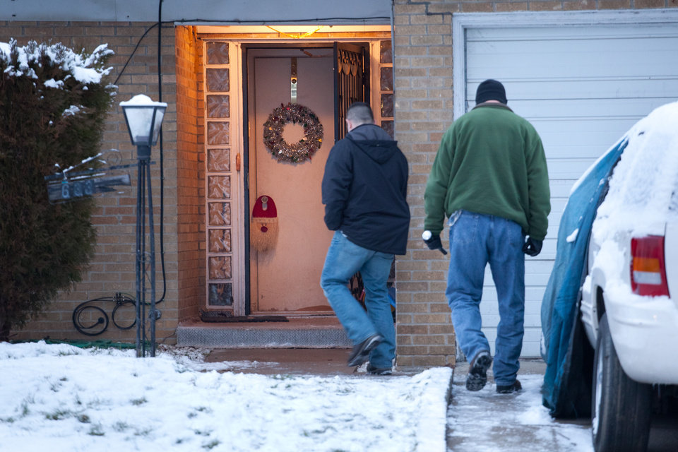 Law enforcement officials enter a home on Tuesday, Dec. 25, 2012 in Flint, Mich. Authorities say five people are dead in two separate incidents of what is believed to be accidental carbon monoxide poisoning. (AP Photo/Flint Journal, Griffin Moores)