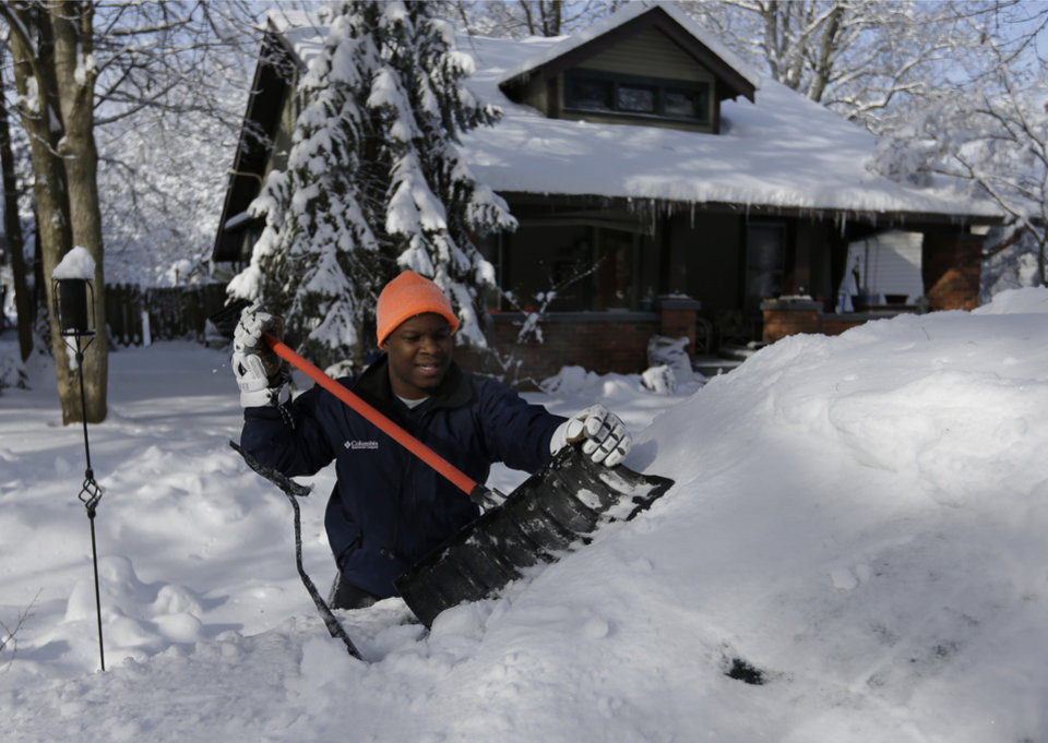 Photo - John Douglas shovels the snow off his car in Indianapolis Monday, Jan. 6, 2014 as temperatures hovered around 10 below zero. More than 12 inches of snow fell on Sunday. (AP Photo/Michael Conroy)