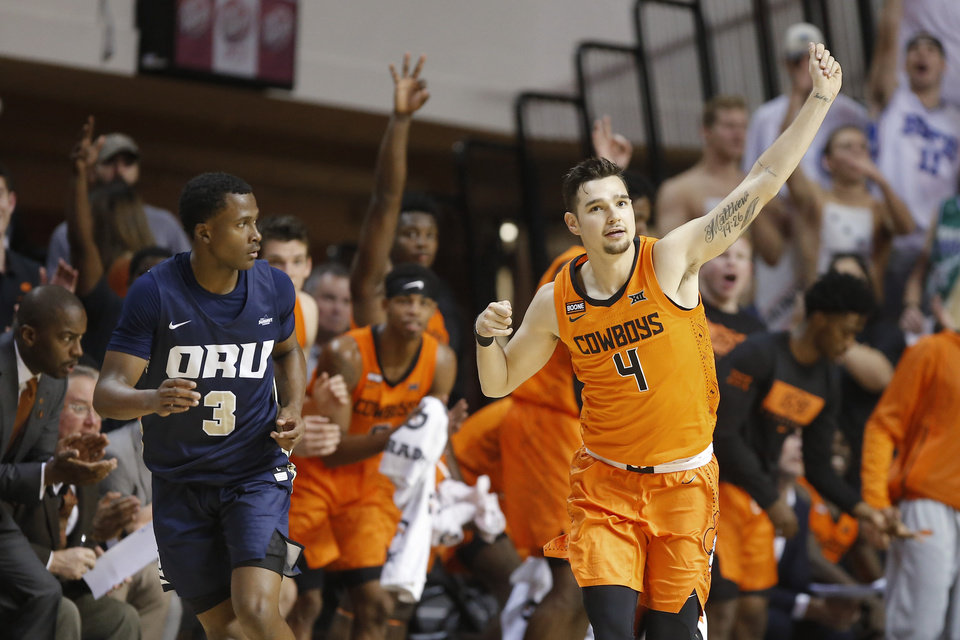 Photo - Oklahoma State's Thomas Dziagwa (4) celebrates after making a basket beside Max Abmas (3) of Oral Roberts during an NCAA basketball game between the Oklahoma State University Cowboys (OSU) and the Oral Roberts Golden Eagles (ORU) at Gallagher-Iba Arena in Stillwater, Okla., Wednesday, Nov. 6, 2019. Oklahoma State won 80-75. [Bryan Terry/The Oklahoman]