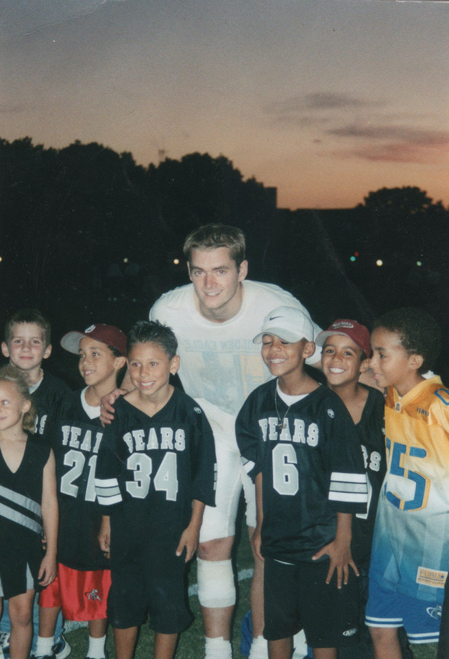 Kendal Thompson, wearing No. 6, and teammates from his 8-year-old football team pose with then-quarterback Josh Heupel during a 2000 football practice. PHOTO PROVIDED