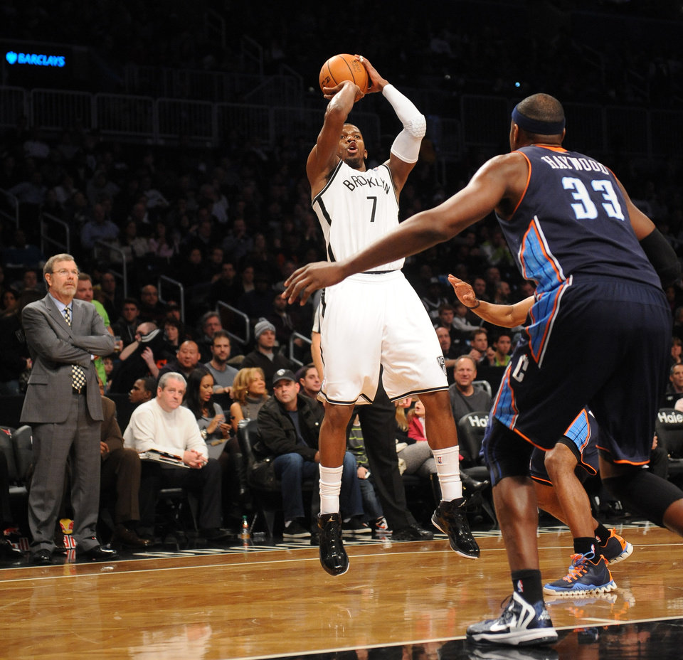 Brooklyn Nets interim head coach P.J. Carlesimo watches Joe Johnson (7) shoots over Charlotte Bobcats' Brendan Haywood (33) in the first half of an NBA basketball game on Friday, Dec., 28, 2012 at Barclays Center in New York. (AP Photo/Kathy Kmonicek)