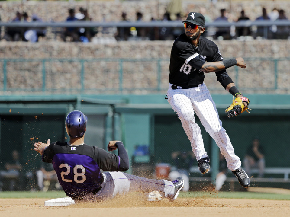 Photo - Chicago White Sox shortstop Alexei Ramirez avoids the slide of Colorado Rockies' Nolan Arenado (28) after relaying to first to complete a double play on Justin Morneau in the fourth inning of a spring exhibition baseball game Tuesday, March 25, 2014, in Glendale, Ariz. (AP Photo/Mark Duncan)