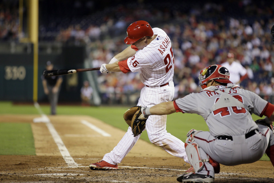Photo - Philadelphia Phillies' Cody Asche follows through after hitting a two-run single off Washington Nationals starting pitcher Gio Gonzalez during the fourth inning of a baseball game, Tuesday, Sept. 3, 2013, in Philadelphia. At right is Wilson Ramos. (AP Photo/Matt Slocum)