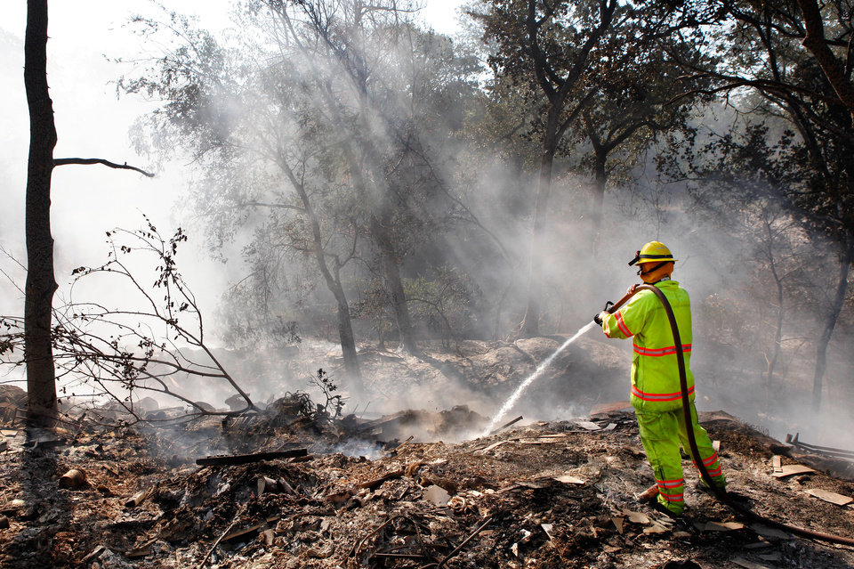 Photo - Tuttle firefighter Joseph Lashbrook sprays water on smoldering embers and hot ashes behind a home that burned to the ground Tuesday after wildfires ravaged land and property that stretched from NE 50 on the south to Hefner Road on the north.  The fire extended from Sooner Road to Midwest Blvd.    Photo taken Wednesday, Aug. 31, 2011. Photo by Jim Beckel, The Oklahoman
