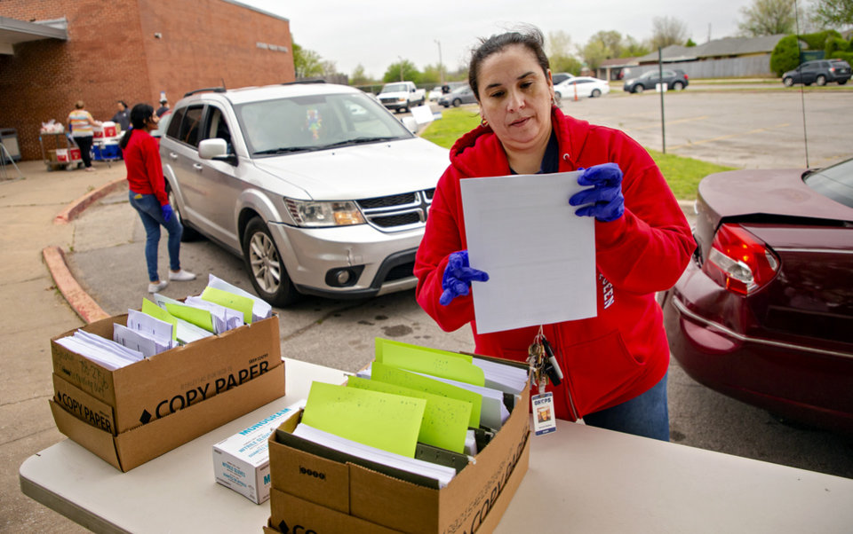 Photo - Prairie Queen Elementary teachers  Veronica Ramirez, right, and Jocelyn Aguilar handout distant learning packets at the school in Oklahoma City, Okla. on Monday, April 6, 2020. Oklahoma City Public Schools and other districts across the state began their first day of handing out the distant learning packets.    [Chris Landsberger/The Oklahoman]