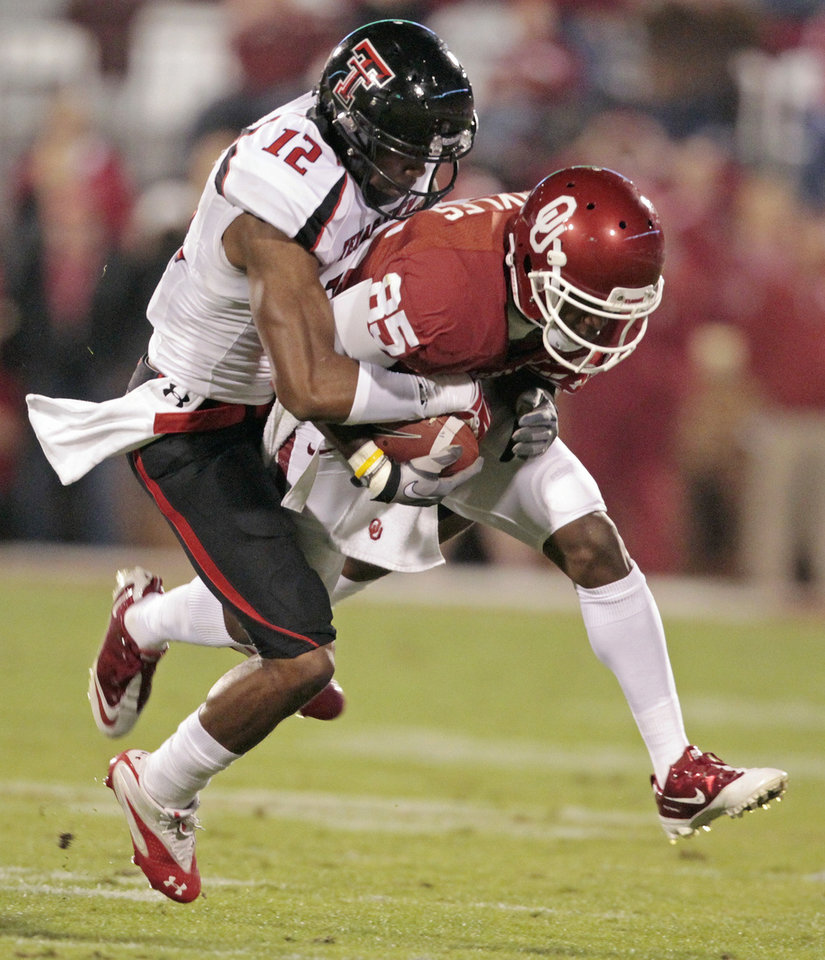 Photo - Texas Tech's D.J. Johnson (12) strips the ball from Oklahoma's Ryan Broyles (85) after a long pass play during the first half of the college football game between the University of Oklahoma Sooners (OU) and Texas Tech University Red Raiders (TTU) at the Gaylord Family-Memorial Stadium on Saturday, Oct. 22, 2011. in Norman, Okla. Photo by Steve Sisney, The Oklahoman