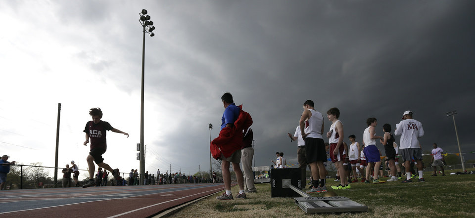 Photo - A high school student athlete finishes the 400 meter run against threatening skies in Montgomery, Ala., Monday, March 18, 2013. The track meet at Montgomery Academy was cancelled as the state long weather front of severe thunderstorms approached. (AP Photo/Dave Martin)