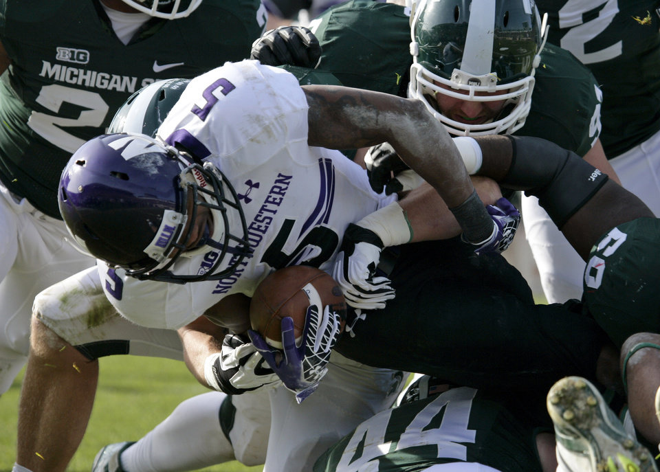 Photo -   Northwestern's Venric Mark (5) is stopped by Michigan State's Tyler Hoover, top right, Marcus Rush (44), and Max Bullough, center rear, during the first quarter of an NCAA college football game, Saturday, Nov. 17, 2012, in East Lansing, Mich. (AP Photo/Al Goldis)