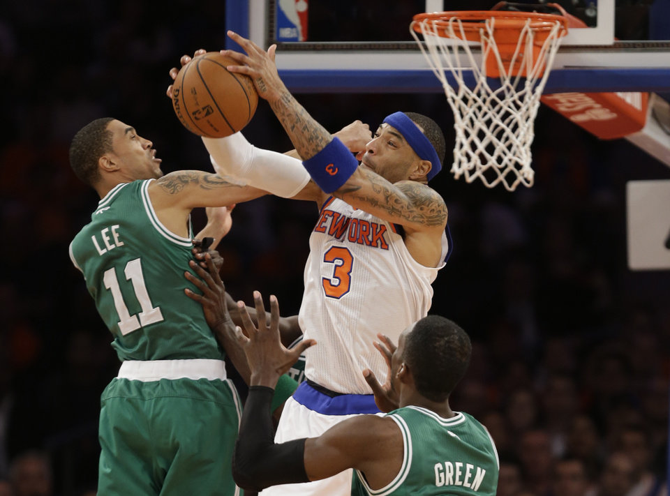 Photo - New York Knicks forward Kenyon Martin (3) grabs a rebound against Boston Celtics guard Courtney Lee (11) and forward Jeff Green during the second half of Game 1 of in the first round of the NBA basketball playoffs in New York, Saturday, April 20, 2013. The Knicks win 85-78. (AP Photo/Kathy Willens)
