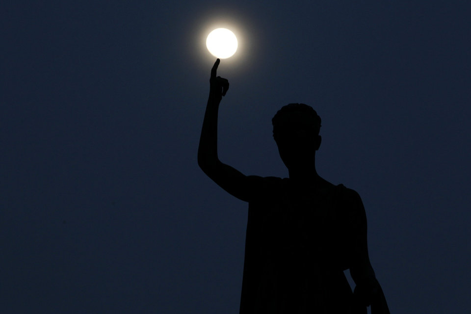Photo - A statue atop a monument representing Cyprus' liberty, seen standing as the moon rises behind, in capital Nicosia, Cyprus, Monday, March 25, 2013. (AP Photo/Petros Giannakouris)