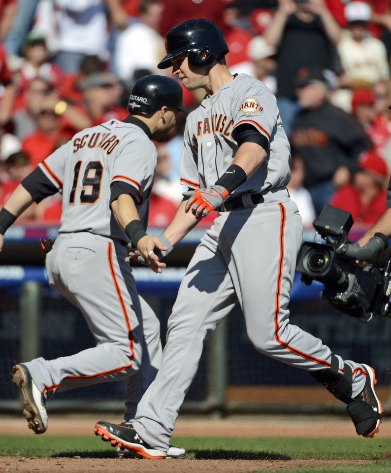 San Francisco Giants' Buster Posey is congratulated by Marco Scutaro (19) after Posey hit a grand slam against the Cincinnati Reds in the fifth inning of Game 5 of the National League division baseball series, Thursday, Oct. 11, 2012, in Cincinnati. (AP Photo/Michael Keating)