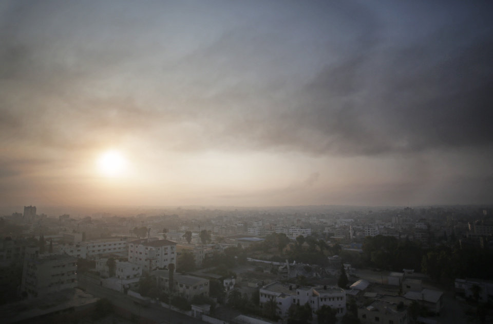 Photo - Smoke from Israeli strikes rises over Gaza City, in the Gaza Strip, Tuesday, July 29, 2014.The overnight strikes came after a day of heavy Hamas-Israeli fighting in which nine children were killed by a strike on a Gaza park where they were playing, according to Palestinian health officials - a tragedy that each side blamed on the other. (AP Photo/Khalil Hamra)