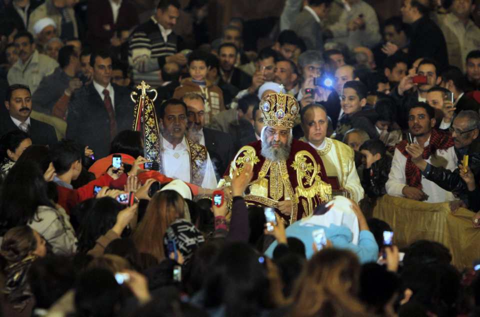 Photo - Pope Tawadros II, the 118th pope of the Coptic Church of Egypt, is greeted by Egyptian Christians as he prepares to lead a midnight Mass on the eve of Egyptian Orthodox Christmas at St. Mark's Cathedral in Cairo, Egypt, late Sunday, Jan. 6, 2013 . (AP Photo/Amr Nabil)