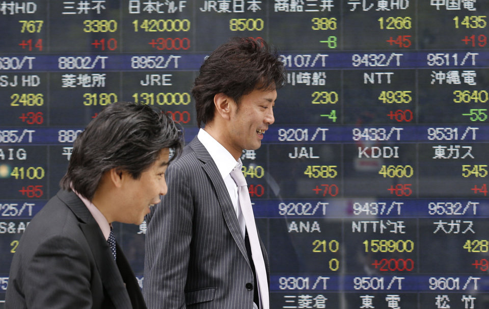 Photo - People walk by an electronic stock board of a securities firm in Tokyo, Thursday, April 25, 2013. Asian stocks rose Thursday as mixed U.S. corporate earnings and a slump in orders for U.S. durable goods convinced investors that central banks would continue efforts to help the global economic recovery. Japan's Nikkei 225 rose 0.5 percent to 13,909.40. (AP Photo/Koji Sasahara)