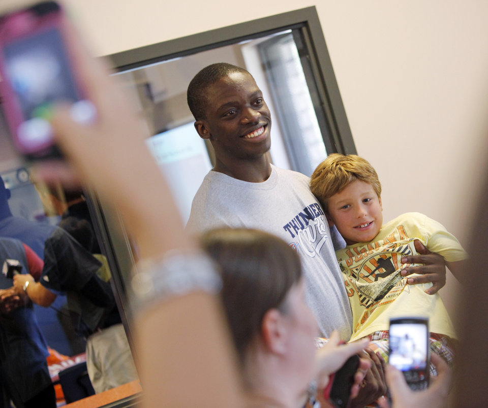 Oklahoma City Thunder draft pick Reggie Jackson picks up Austin Null, 9, as they pose for a photo at the Boys and Girls Club of Oklahoma County in Oklahoma City, Saturday, June 25, 2011. The Thunder selected Reggie Jackson with the 24th pick in this year\'s NBA draft. Photo by Nate Billings, The Oklahoman