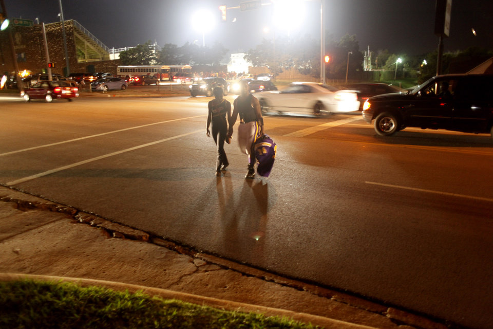A NWC couple cross May Avenue back to the school after the game at the Northwest Classen vs. Western Heights high school football game at Taft Stadium Thursday, September 20, 2012. Photo by Doug Hoke, The Oklahoman