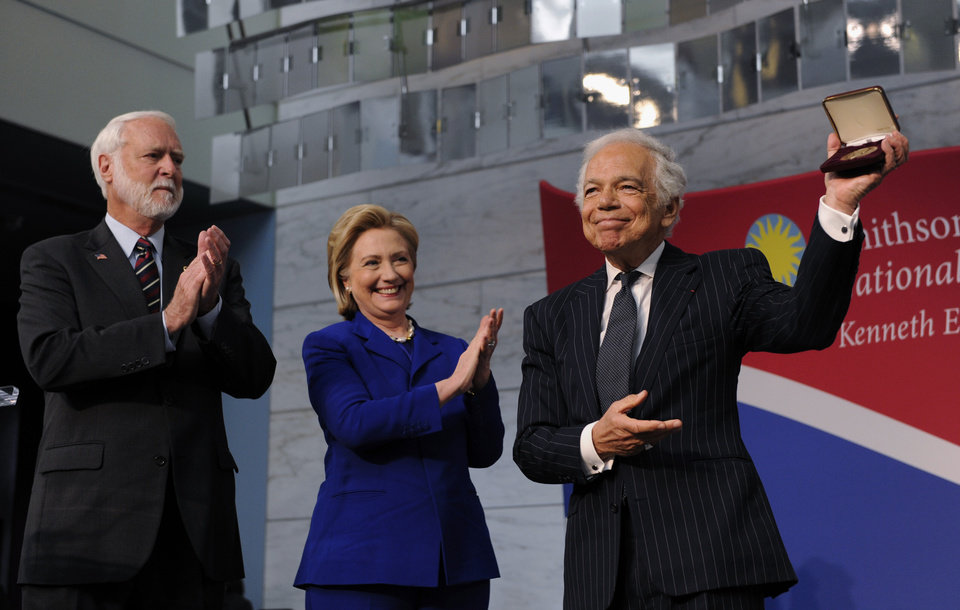 "Photo - Designer Ralph Lauren, right, stands with Smithsonian Secretary G. Wayne Clough, left, and former Secretary of State Hillary Rodham Clinton after receiving the James Smithson Bicentennial Medal ""for his embodiment of the American experience through the medium of fashion, design and philanthropy"