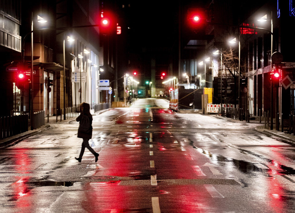 Photo -  A woman crosses a deserted street in central Frankfurt, Germany, Monday, Feb. 10, 2020. A heavy storm with rain hits big parts of Germany. (AP Photo/Michael Probst)