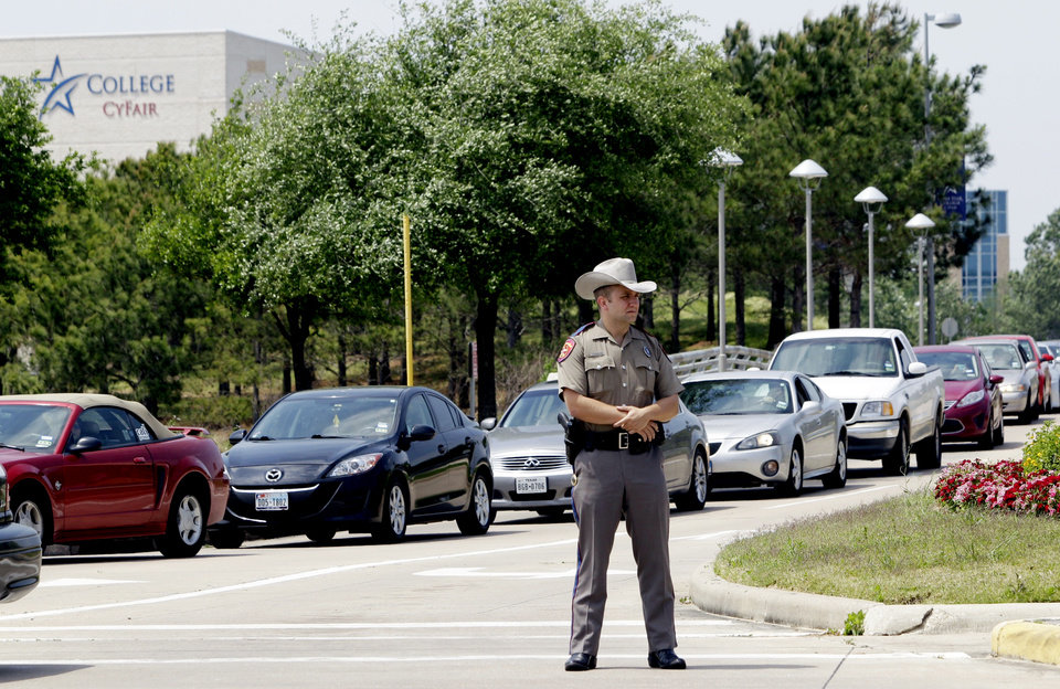 Photo - A Texas State Trooper stands at an entrance as vehicles leave from the Cy-Fair campus of Lone Star Community College in Cypress, Texas on Tuesday, April 9, 2013.  More than a dozen people were wounded when a suspect went building-to-building in an apparent stabbing attack at the college campus authorities said.  The attack on the Lone Star Community College System's campus in Cypress sent at least 12 people to area hospitals, including four people taken by helicopter, according to Cy-Fair Volunteer Fire Department spokesman Robert Rasa.  (AP Photo/Houston Chronicle, Melissa Phillip)  MANDATORY CREDIT