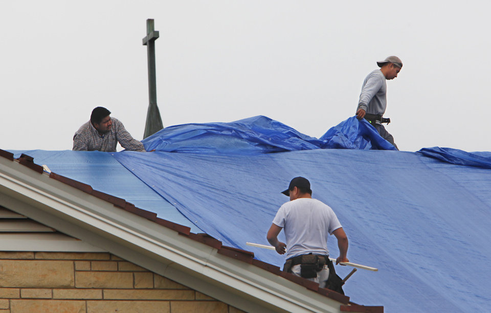 Photo - HAIL STORM / DAMAGE / REPAIR: Workers cover the roof of the United Methodist Church of Nichols Hills that was damaged by Sunday's hail storm, Monday, May 17, 2010.    Photo by David McDaniel, The Oklahoman     ORG XMIT: KOD