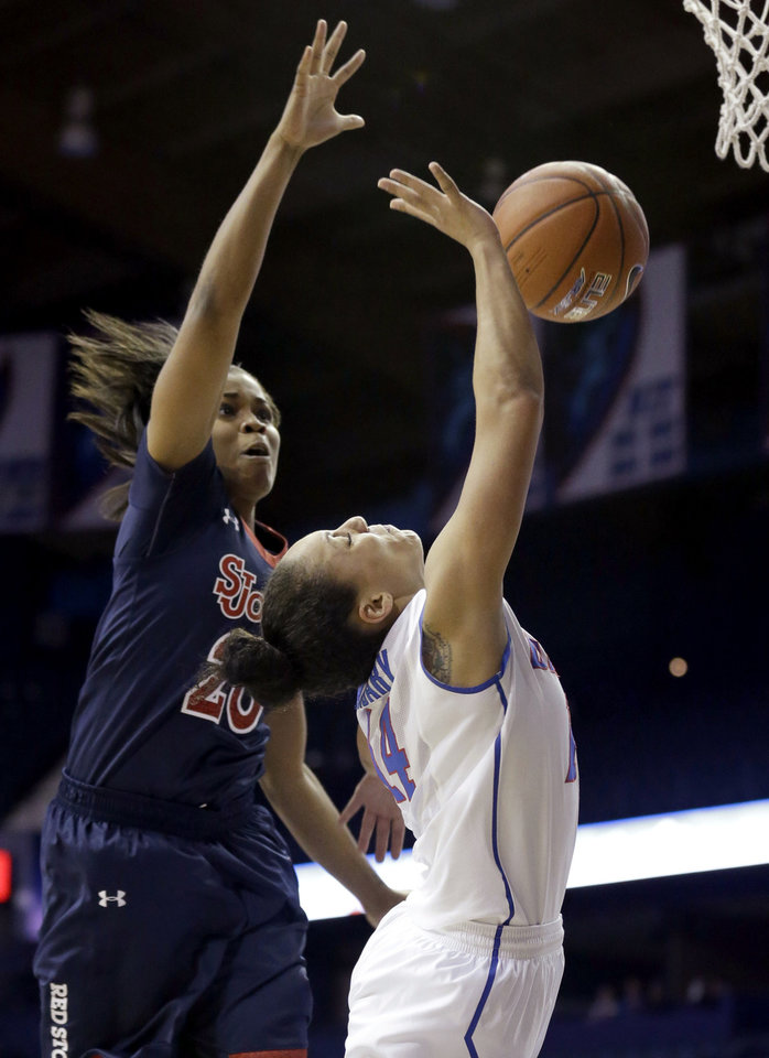 Photo - DePaul guard Jessica January, right, drives to the basket past St. John's guard Keylantra Langley during the second half of an NCAA college basketball game in the final of the 2014 Big East women's basketball tournament in Rosemont, Ill., Tuesday, March 11, 2014. DePaul won 65-57. (AP Photo/Nam Y. Huh)