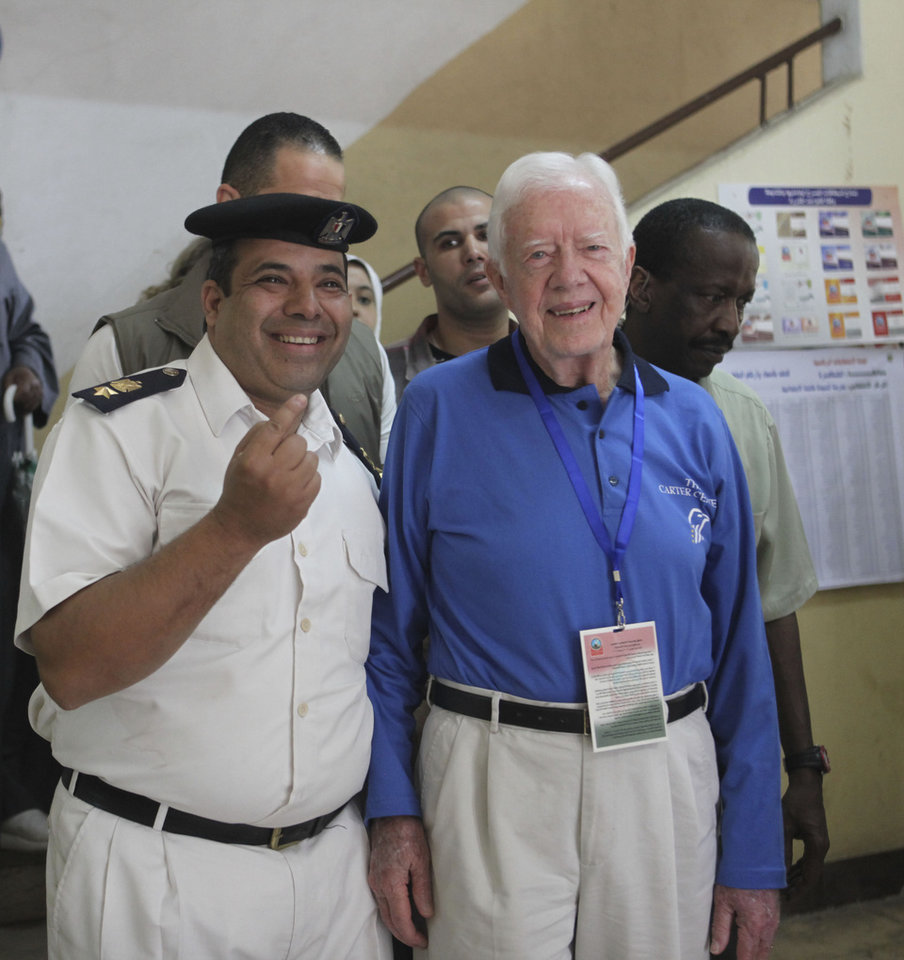 Photo -   Former U.S. President Jimmy Carter, right, poses with an Egyptian policeman inside a polling station in the Sayeda Aisha neighborhood of Cairo, Egypt, Wednesday, May 23, 2012. The Carter Center is in Egypt to monitor the presidential elections. Egyptians went to the polls on Wednesday morning to elect a new president after the fall of ex-President Hosni Mubarak last year.(AP Photo/Thomas Hartwell)