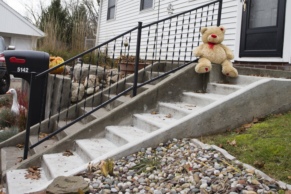 A lone teddy bear sits on the steps of the home where three children, their uncle, and their grandmother were found dead inside a garage Monday in what appears to be a murder-suicide amid a custody dispute in Toledo, Ohio, Tuesday, Nov. 13, 2012. (AP Photo/Rick Osentoski)