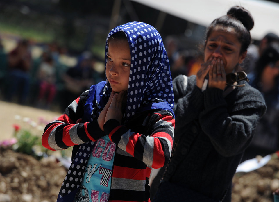 Photo - Two young girls pray at the cemetery in the coal miners' town of Soma, Turkey, Sunday, May 18, 2014. Eighteen people, including mining company executives, have been detained as Turkish officials investigate the mining disaster that killed 301 people, a domestic news agency reported Sunday. (AP Photo/Emre Tazegul)