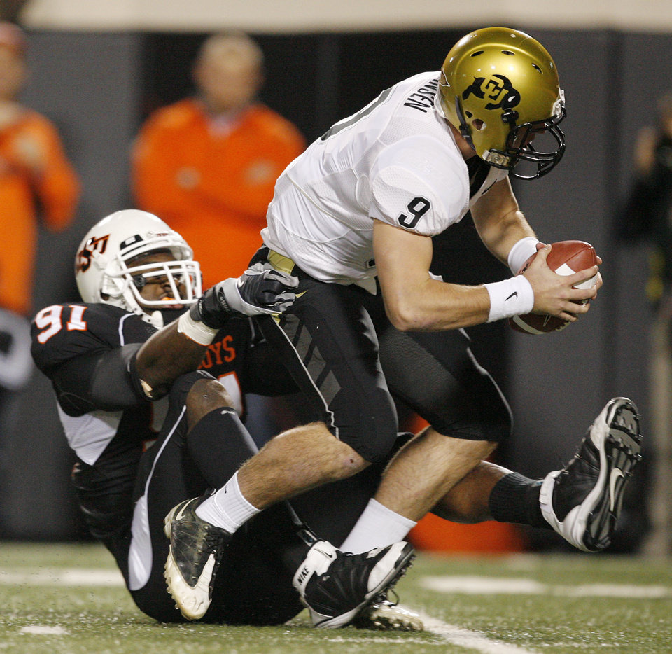 Photo - OSU's Ugo Chinasa (91) sacks Colorado's Tyler Hansen (9) in the first quarter during the college football game between Oklahoma State University (OSU) and the University of Colorado (CU) at Boone Pickens Stadium in Stillwater, Okla., Thursday, Nov. 19, 2009. Photo by Nate Billings, The Oklahoman ORG XMIT: KOD