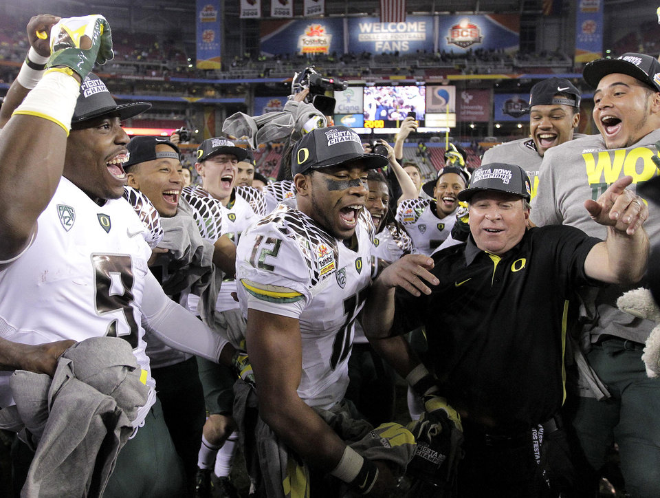 Photo - Oregon players celebrate at mid field after the Fiesta Bowl NCAA college football game, Thursday, Jan. 3, 2013, in Glendale, Ariz. Oregon won 35-17.(AP Photo/Matt York)
