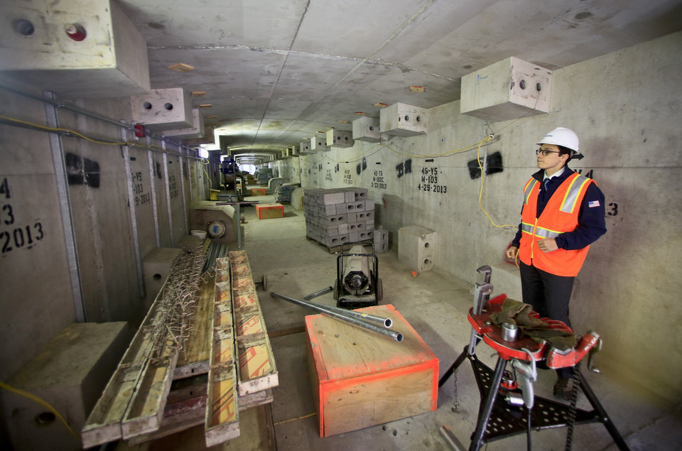 Photo - Berkay Baykal, a project manager on the Brookfield Manhattan West construction project, tours inside a bridge-like concrete span on the project site, Wednesday April 16, 2014 in New York.  Before it becomes a seamless tunnel, a giant crane called