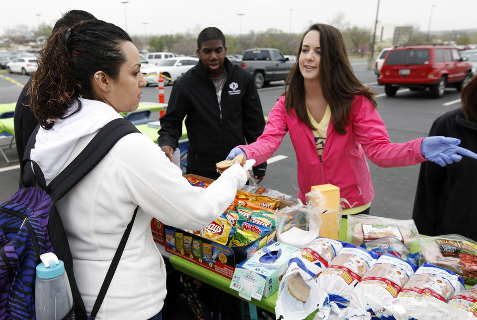 Photo - Liha Villaneuva takes a sandwich from student volunteers LV Crutchar, center, and Jennifer Davis.  Photo By Paul Hellstern, The Oklahoman