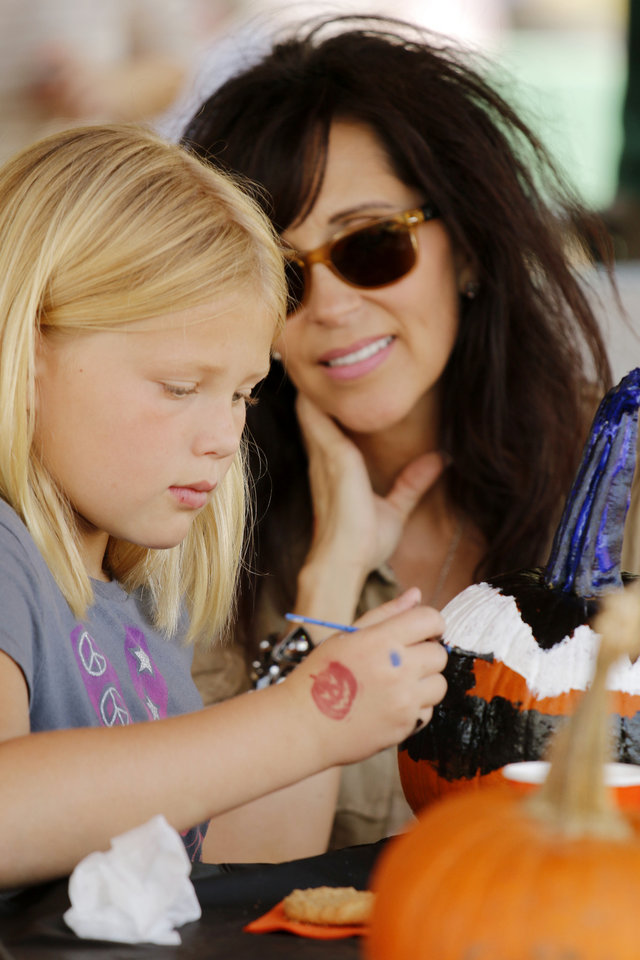 Photo - Tonya Roby, of Edmond, watches her granddaughter, Claire Weston, 9, paint a pumpkin in the Pumpkinville exhibit at the Mryiad Botanical Gardens during a preview party on Friday. PHOTO BY DOUG HOKE, THE OKLAHOMAN  DOUG HOKE - THE OKLAHOMAN