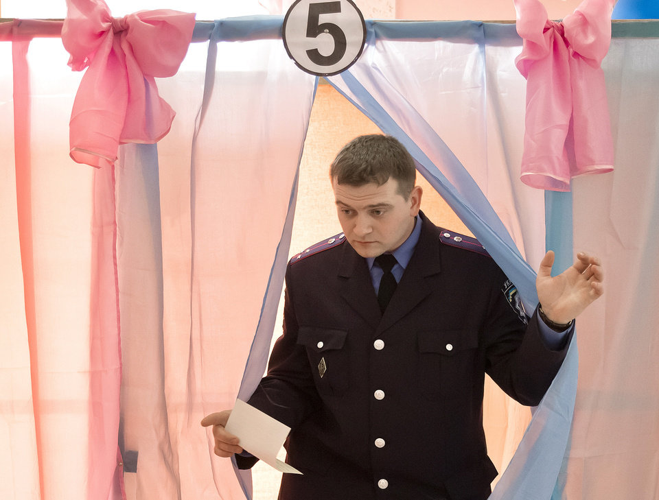 Photo - An Ukrainian policeman exits a voting booth after casting his vote in Perevalne, Ukraine, Sunday, March 16, 2014. Residents of Ukraine's Crimea region are voting in a contentious referendum on whether to split off and seek annexation by Russia. (AP Photo/Vadim Ghirda)