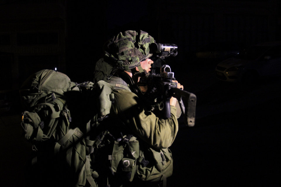 Photo - Israeli soldiers patrol during a military operation to search for three missing Israeli teenagers near the West Bank city of Hebron, Sunday, June 15, 2014. A terror group abducted three teens, including an American, who disappeared in the West Bank, Israel's Prime Minister Benjamin Netanyahu said Saturday, as soldiers searched the territory to find them. (AP Photo/Nasser Shiyoukhi)