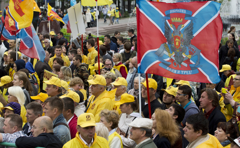 Photo - Members of the Just Russia Party hold flags from the self-proclaimed Republic of Novorossia, right, during a rally in support of pro-Russian insurgents in eastern Ukraine, Moscow, Friday, July 11, 2014. (AP Photo/Pavel Golovkin)