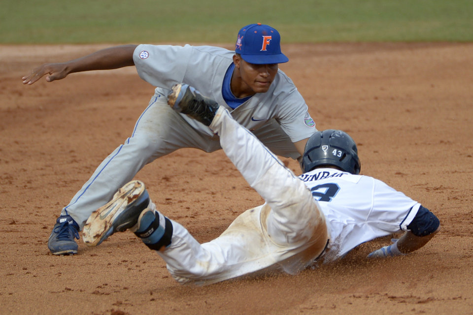 Photo - North Carolina's Korey Dunbar, front, is tagged out by Florida shortstop Richie Martin at second base while trying to stretch a hit into a double during the third inning of an NCAA college baseball regional tournament game in Gainesville, Fla., Saturday, May 31, 2014.(AP Photo/Phelan M. Ebenhack)