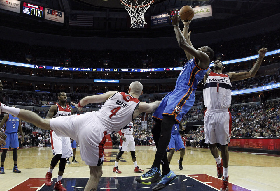 Oklahoma City Thunder forward Kevin Durant, front right, shoots as he is defended by Washington Wizards center Marcin Gortat (4), from Poland, and forward Trevor Ariza (1) in the first half of an NBA basketball game on Saturday, Feb. 1, 2014, in Washington. The Wizards won 96-81. (AP Photo/Alex Brandon)