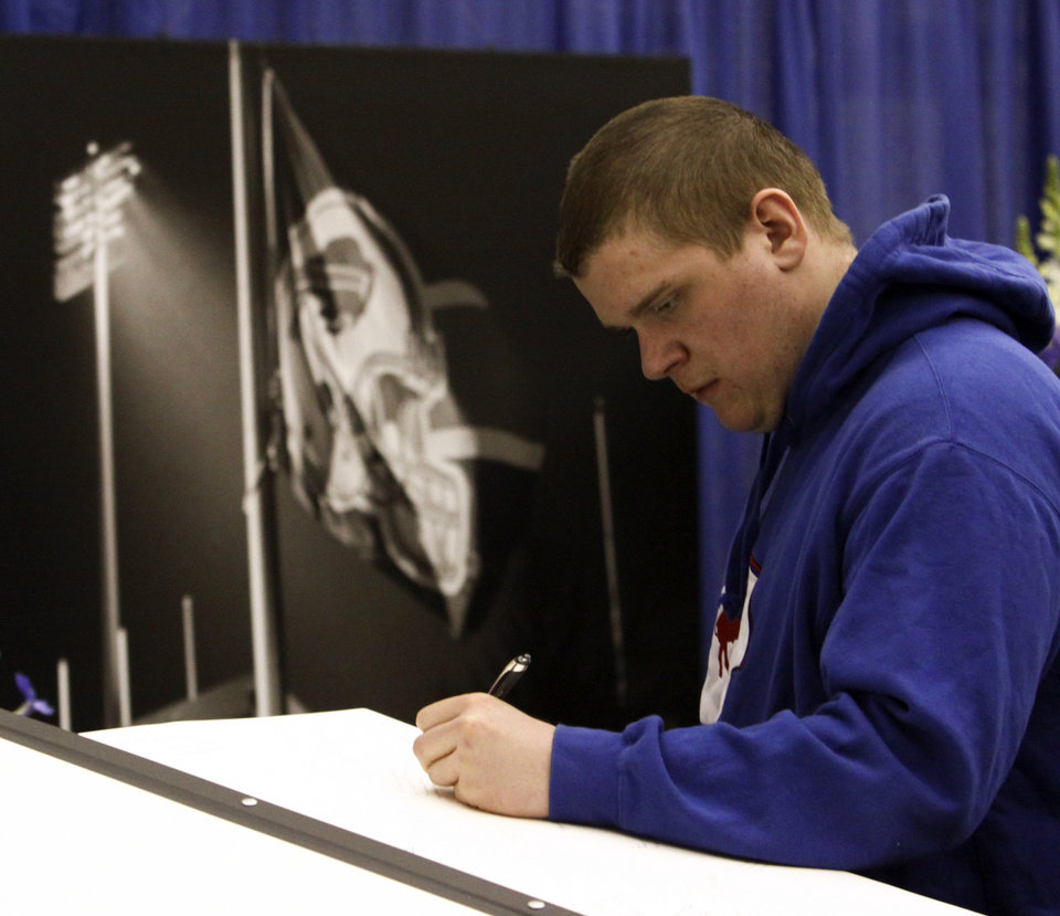 Photo - Andrew Rogacki, of Attica, N.Y., signs a large tribute album during a public memorial and remembrance being held inside the NFL football team's fieldhouse for Buffalo Bills owner Ralph C. Wilson in Orchard Park, N.Y., Saturday, April 5, 2014. Wilson, the team's founder and sole owner, died March 25. (AP Photo/Nick LoVerde)