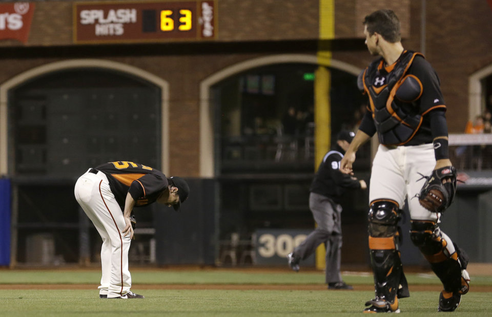 Photo - San Francisco Giants pitcher Tim Lincecum, left, bends forward after being struck by a ball hit by Oakland Athletics' Daric Barton as Giants catcher Buster Posey watches during the fourth inning of a spring exhibition baseball game in San Francisco, Friday, March 28, 2014. (AP Photo/Jeff Chiu)